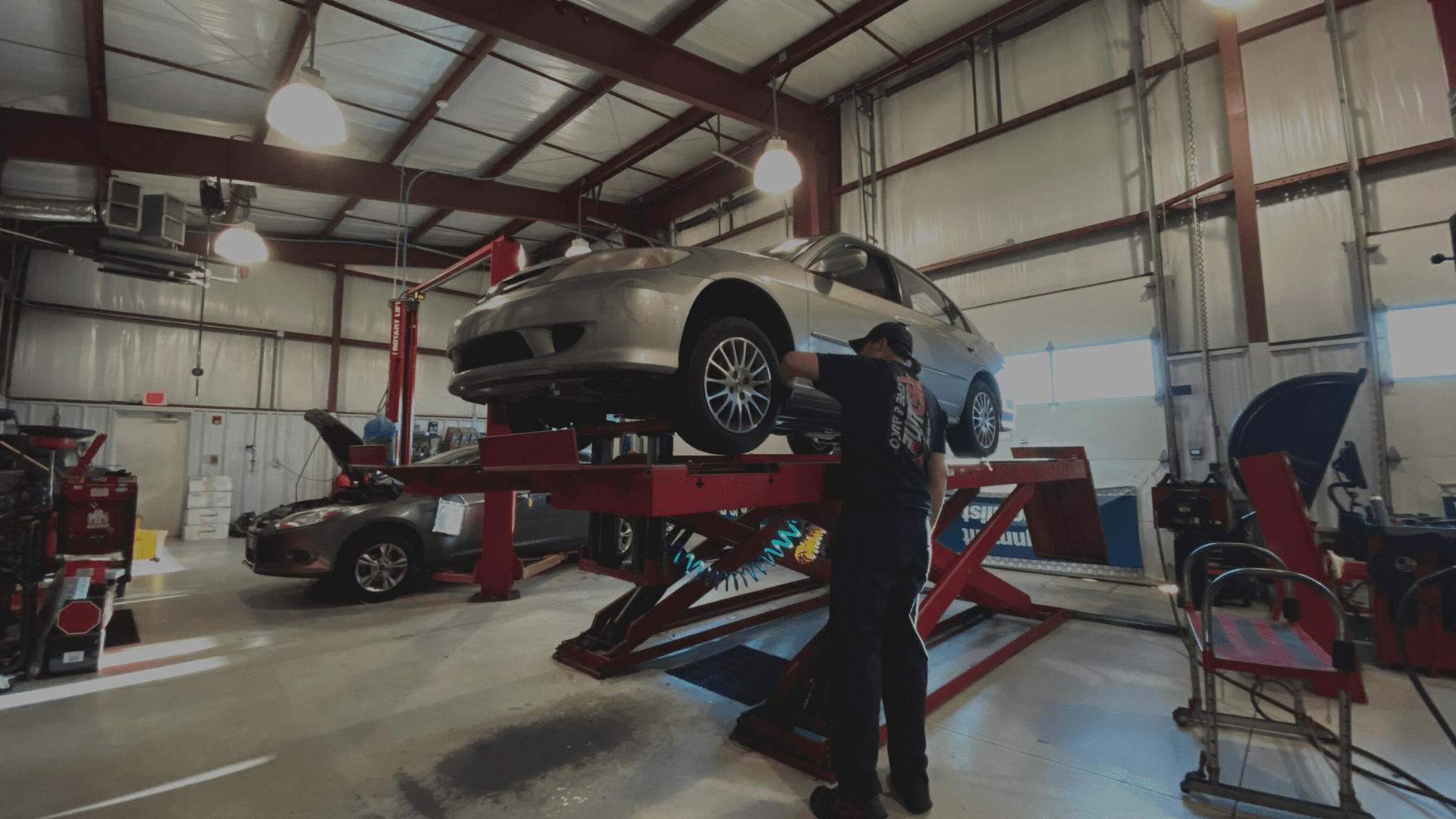 redline tire and auto employee performing auto repair