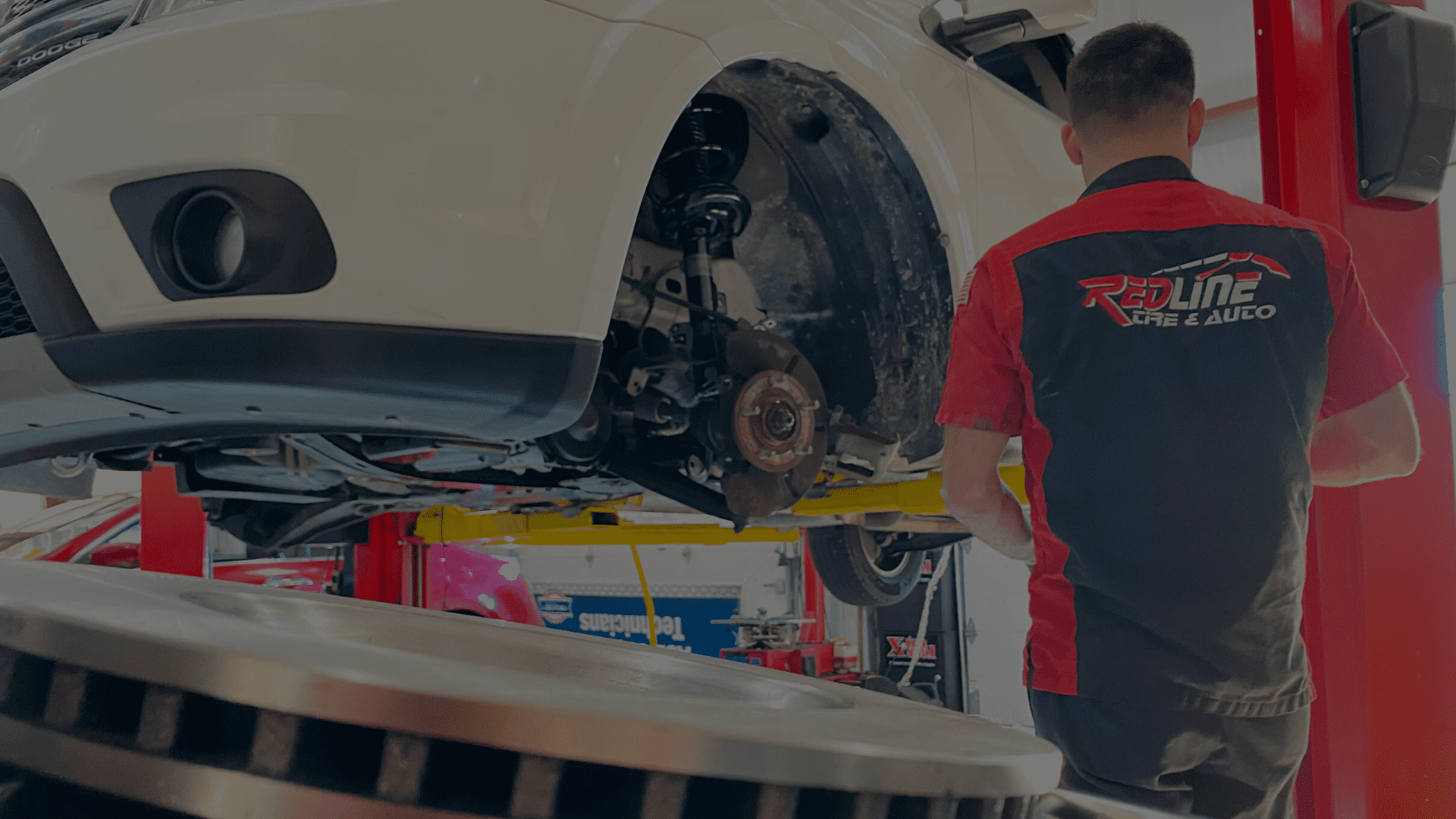 redline tire and auto employee performing brake repairs